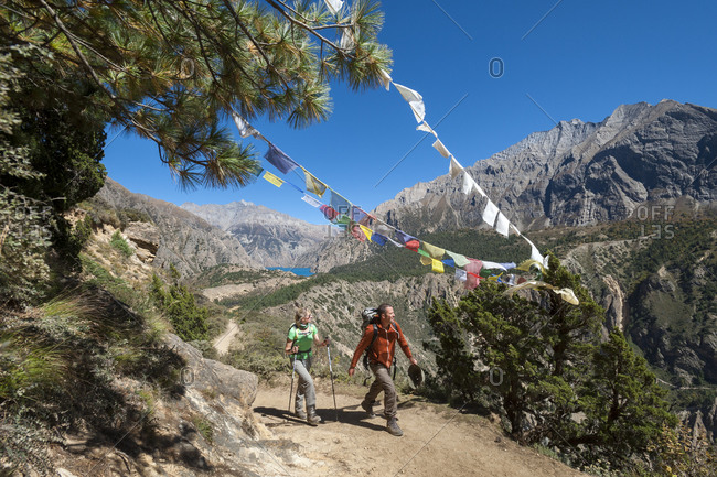 Trekkers passing some prayer flags on the trail in Dolpa in Nepal with a view of Phoksundo lake in the distance