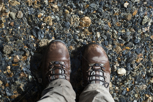 Hiking boots standing in a shallow stream while trekking in Nepal