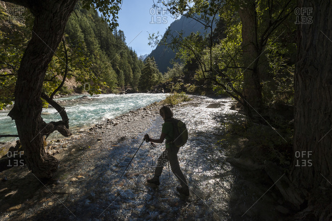 A trekker crosses the shallow part of a river in the Kagmara valley in Dolpa, a remote region of Nepal