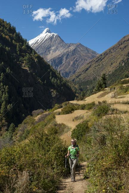 A trekker walks through wheat fields in the Kagmara valley in lower Dolpa, a remote region of Nepal