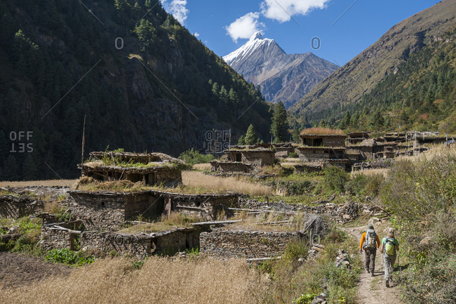 Trekkers pass through a traditional little village surrounded by wheat fields in the Kagmara valley in lower Dolpa, a remote region of Nepal