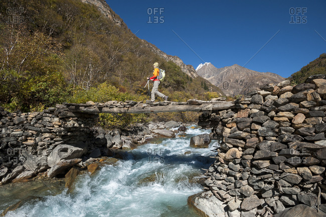 Trekking across a small log bridge in the Juphal valley in Dolpa, a remote region of Nepal