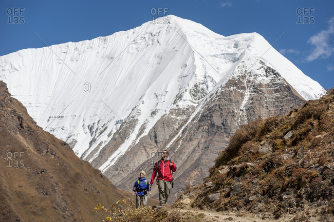 Trekkers walk up the Kagmara valley in Dolpa, a remote region of Nepal, with views of Lhashama in the distance