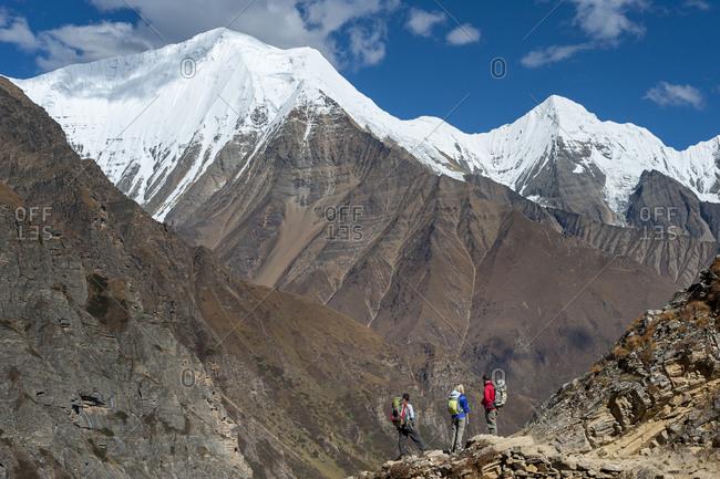 Trekkers admire the peaks of Lhashama and Kanchauni Lekh in the Dolpo region of Nepal.
