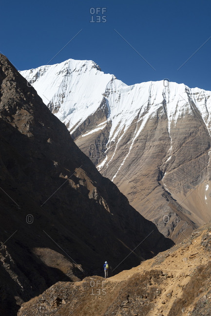 Lone hiker in the Kagmara valley in Dolpa, a remote region of Nepal, with views of Lhashama in the distance