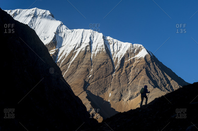 Silhouetted hiker in the Kagmara valley in Dolpa, a remote region of Nepal, with views of Lhashama in the distance