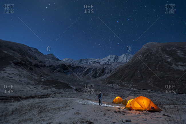 In the little explored Juphal valley in the remote Dolpa region of Nepal, a man stands outside his tent on a cold night to look at the stars