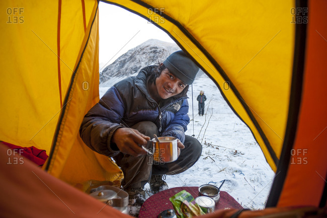 Kagmara valley, Dolpa, Nepal - October 10, 2012: A sherpa brings a cup of tea to a tent on a trek in Nepal
