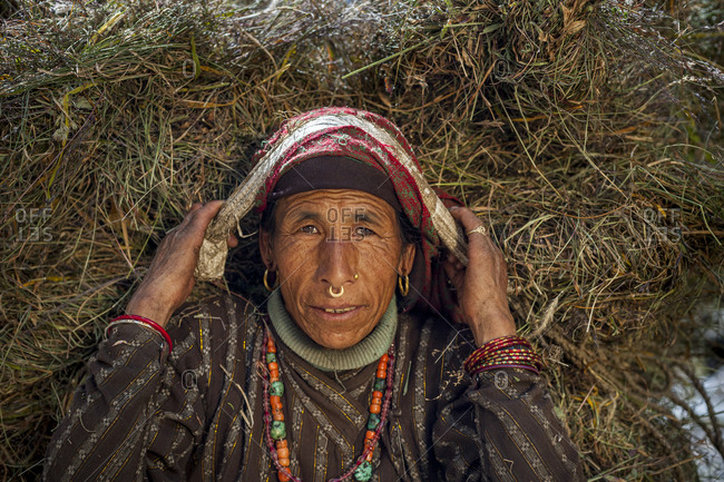 A old woman from Dolpa in Nepal carries fodder on her head with a Namlo or head strap