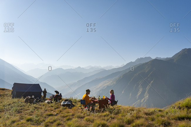 A couple eat breakfast on a secluded hillside in the Juphal valley while trekking in Dolpa, a remote region of Nepal