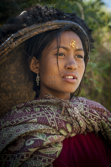 A woman from Dolpa wearing traditional clothes and carrying a bamboo rice pan for winnowing rice on her head