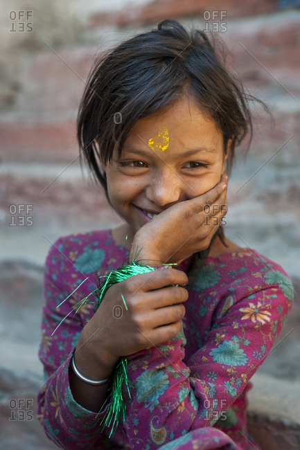 A pretty little girl in the remote Dolpa region of Nepal wearing Tikka on her forehead to celebrate a festival