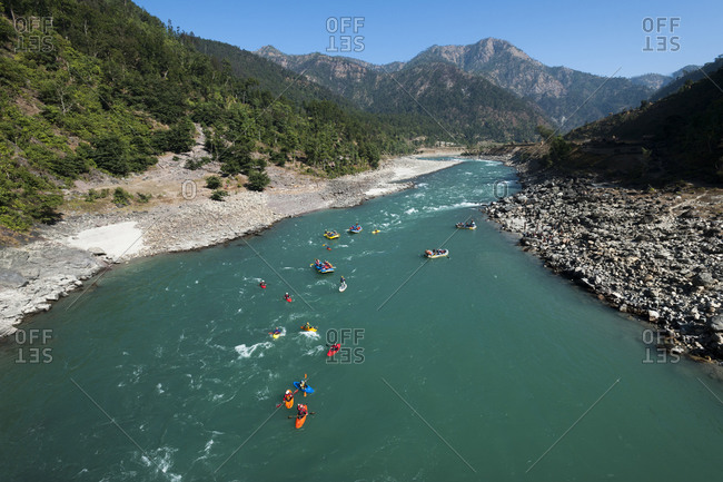 Rafts and kayaks drift down the Karnali river in west Nepal