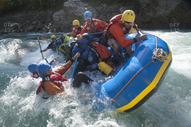 A raft flips over going through rapids on the Karnali river in Nepal