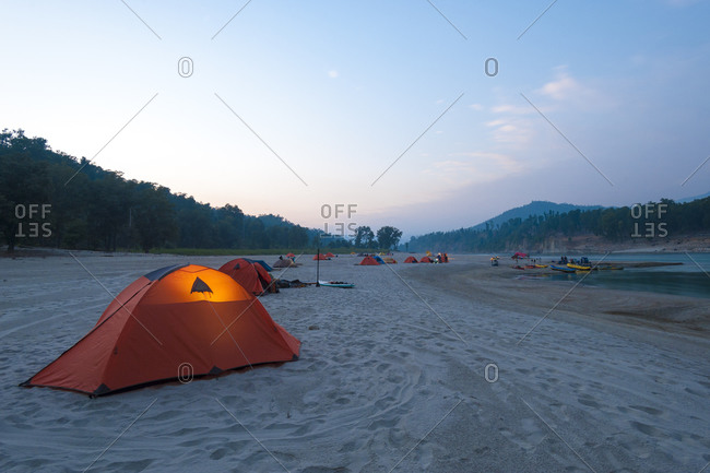 A tent glows in the twilight during a rafting expedition down the Karnali river in far west Nepal