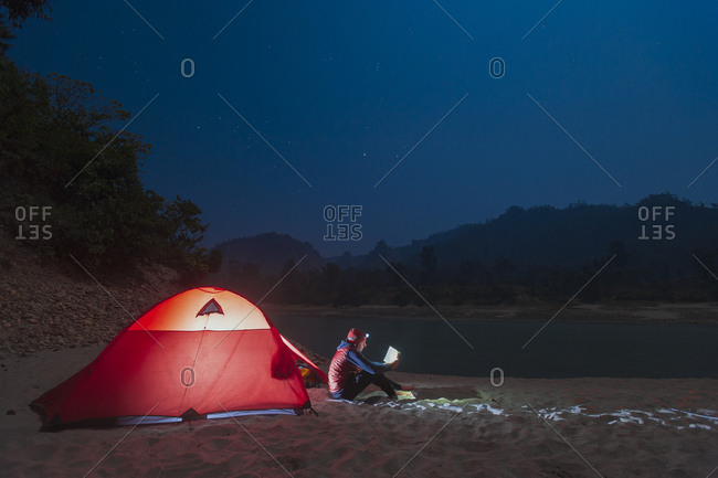 Reading by head lamp outside a tent during a river rafting trip on the Karnali river in west Nepal