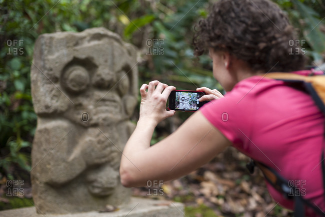 A woman takes a photo of an ancient statue with a smartphone at San Agustin in Colombia