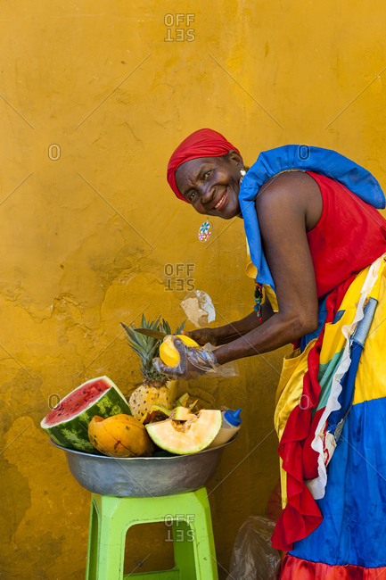 Woman dressed in traditional clothes cutting and selling fruit in the colorful old town of Cartagena.