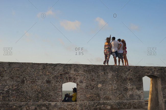 Cartagena, Caribbean Coast Region, Colombia - February 10, 2013: People look out from the top of a sea wall in the old town of Cartagena on the northern Caribbean coast