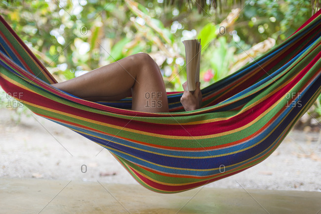 A girl relaxes and reads her book while hanging in a hammock on the beach