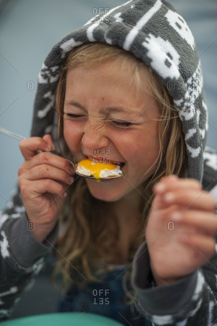 A little girl bites into a gooey egg yolk