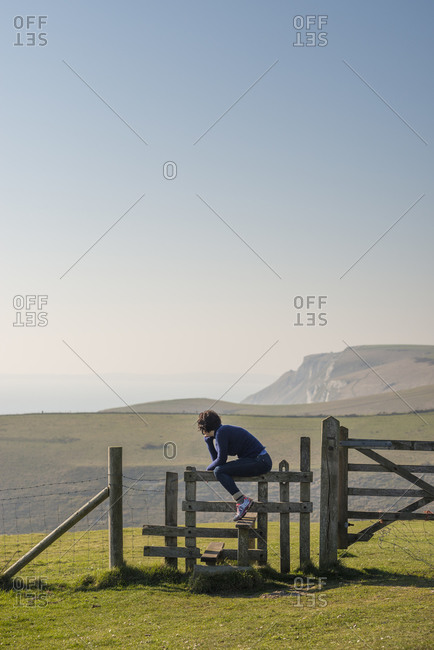 A perfect sunny day in Dorset on the south coast of England. A woman looks out to sea while taking a rest on a stile.