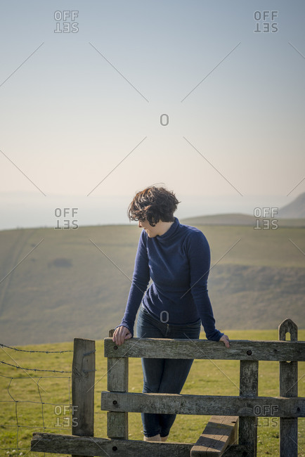 A perfect sunny day in Dorset on the south coast of England. A woman looks out to sea while standing on a stile