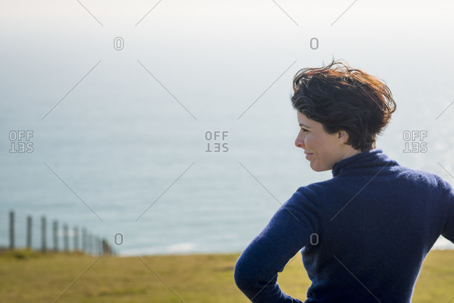 A woman looks out to sea on a perfect sunny day in Dorset on the south coast of England