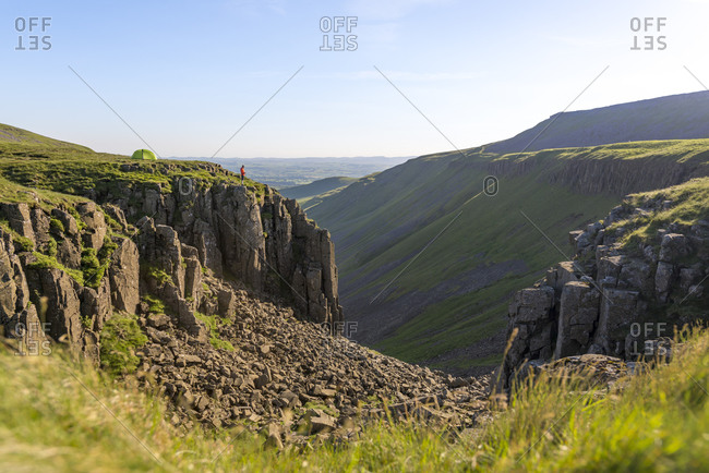 A man hiking the Pennine Way looks out near his tent to the huge escarpment in the Yorkshire Dales called Highcup Nick
