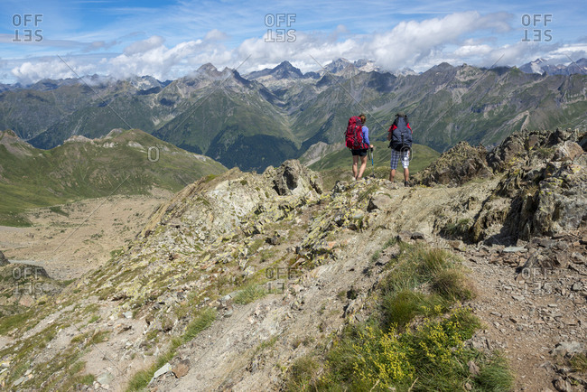 Hikers look out over the Pyrenees from the top of Pic Peyreget on the GR10 trekking trail
