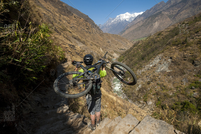 A mountain biker carrying his bike stops to look at the view of Sringi Himal