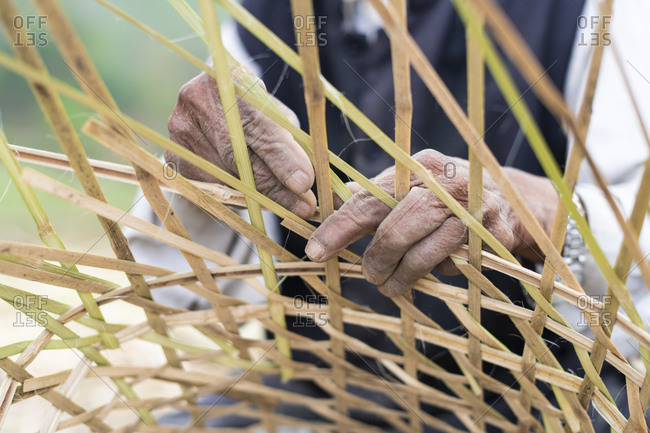 A old Nepali man makes a traditional basket called a Doko by weaving bamboo