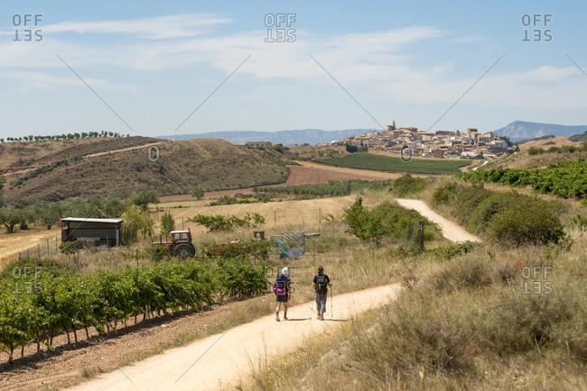 Pilgrims walking the trek called the Camino de Santiago, also known as The Way towards little village of Cirauqui