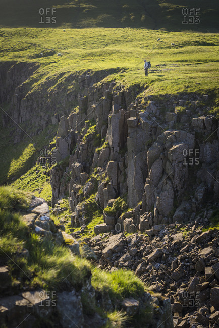 A man hiking the Pennine Way looks out to the huge escarpment in the Yorkshire Dales called Highcup Nick