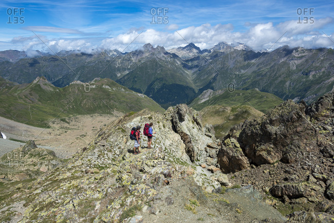 Walkers stand on the top of Pic Peyreget while hiking the GR10 trekking trail