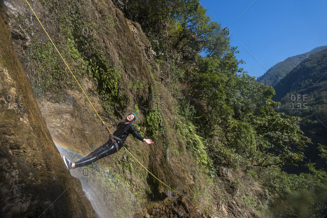 Repelling down a waterfall while canyoning at The Last Resort in Nepal