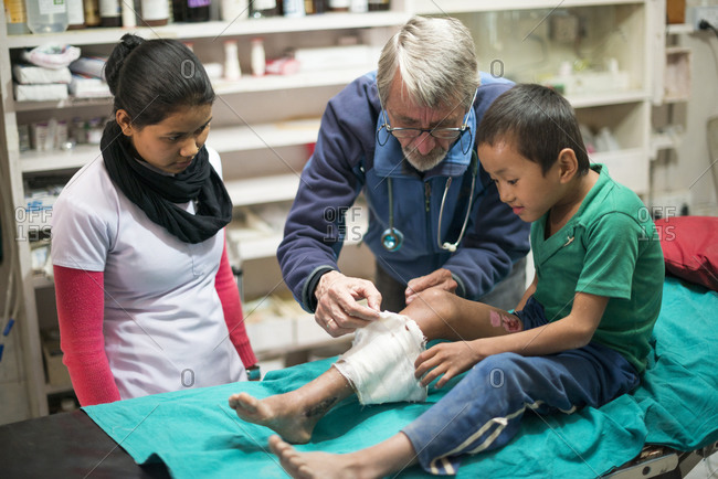 A doctor checks how a boys skin graft leg is healing, at a small hospital in Nepal