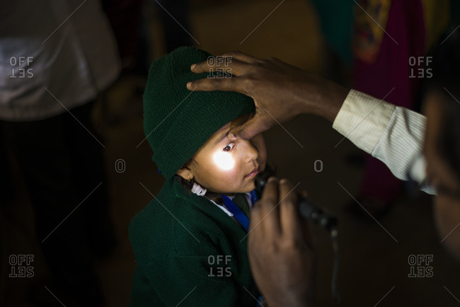 A doctor looks at a baby's eye with a torch at a hospital in Nepal