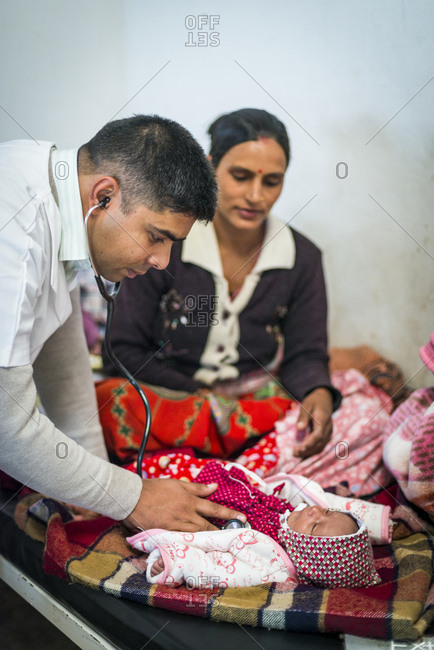 Myagdi, Beni district, Nepal - November 26, 2013: A general practitioner checks a patient's baby with a stethoscope at Myagdi hospital