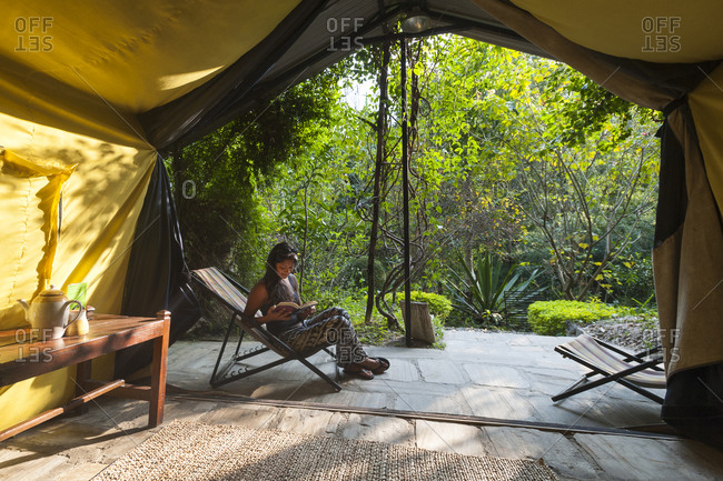 Kodari, Central region, Nepal - October 11, 2012: A girl relaxes outside her cabana tent at The Last Resort in Nepal