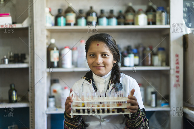 A young woman working in a laboratory in a hospital in Nepal carries test tubes