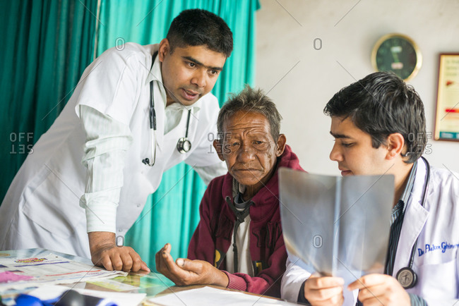 Doctors discuss an x-ray with a patient in a rural hospital in Nepal