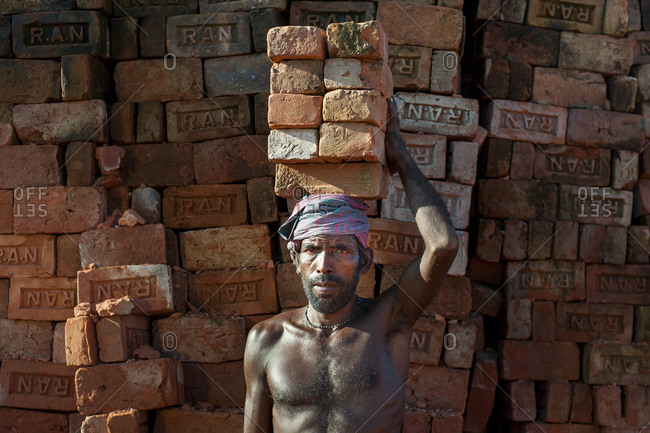 A man laboring in a brick factory will carry up to 50 Kilos of bricks by balancing them on his head