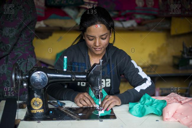 Myagdi, Myagdi, Beni district, Nepal - November 26, 2013: A woman works on a sewing machine in a village