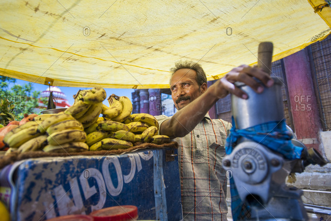 A fruit seller prepares a juice from his stall of fresh fruit