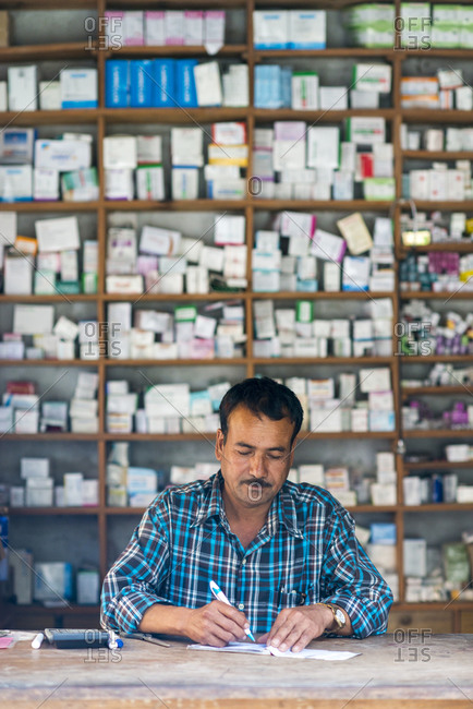 A man working in a dispensary next to a hospital in west Nepal
