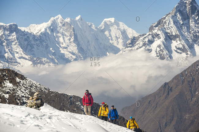 A climbing team make their way to Ama Dablam base camp in the Everest region of Nepal with views of Kantega and Thermserku in the distance