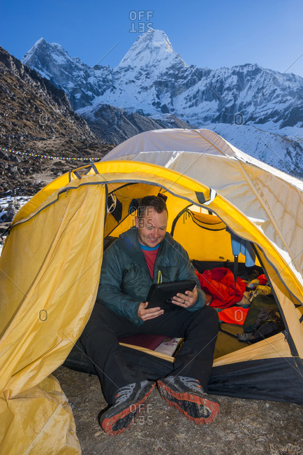 A climber at Ama Dablam base camp in the Everest region of Nepal checks his email on a mobile device during his acclimatization period
