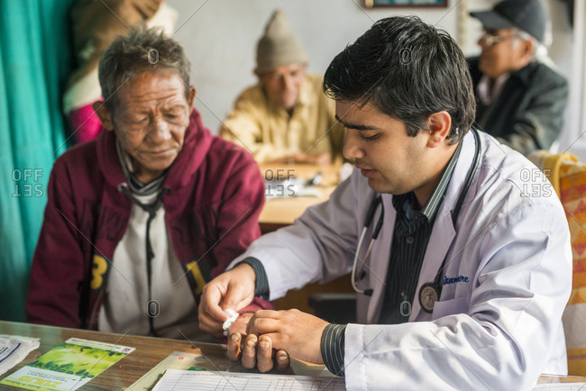 Myagdi, Beni district, Nepal - November 27, 2013: Doctors discuss an x-ray with a patient at Myagdi hospital