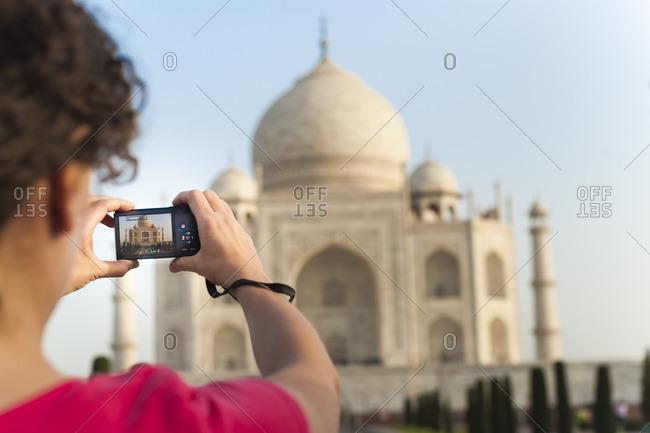 Uttar Pradesh, India - May 3, 2012: A woman takes a photo of the Taj Mahal